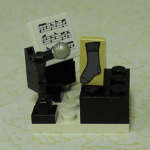 Lego model of a sock singing into a microphone with sheet music on a stand