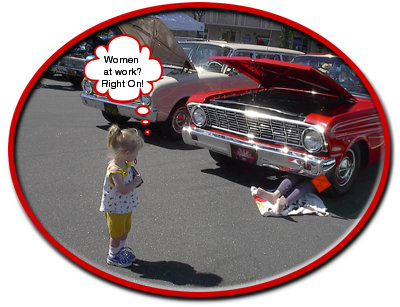 female mannequin dressed like a mechanic under the front end of a shiny red Falcon, Women at Work sign hanging from the bumper